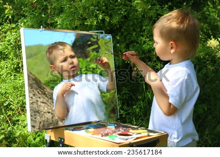 funny kid draws a picture on the mirror - stock photo