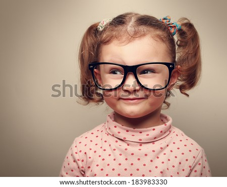 Funny kid girl in glasses looking on empty copy space and thinking. Instagram effect - stock photo