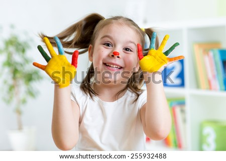 Funny kid girl with hands painted in colorful paint - stock photo