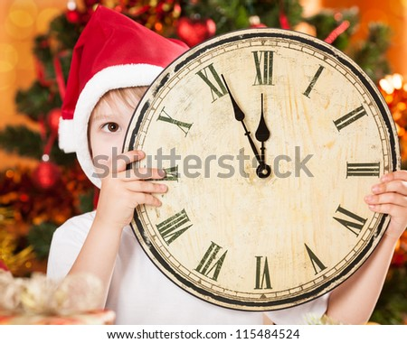 Funny kid hiding by vintage wooden clock against decorated Christmas tree - stock photo
