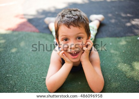 Funny kid sitting on ground in outdoors playground