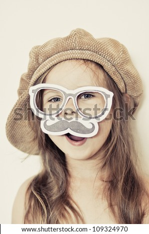Funny kid wearing a fake mustache and cap - stock photo