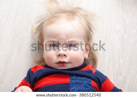 Funny kid with blond hairstyle