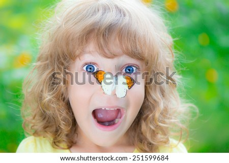 Funny kid with butterfly in spring park. Happy child playing outdoors - stock photo