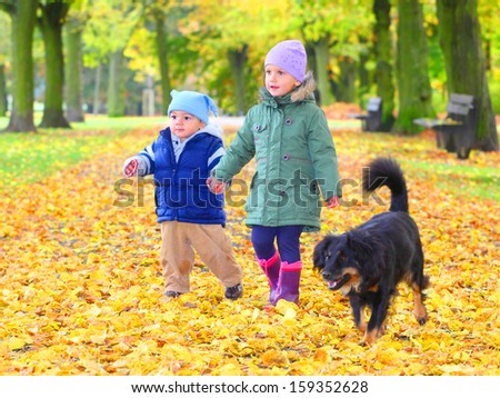 Funny kid with dog walking in yellow foliage. Autumn in the city park. - stock photo