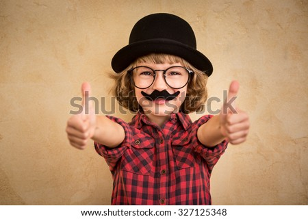 Funny kid with fake mustache. Happy child playing in home  - stock photo