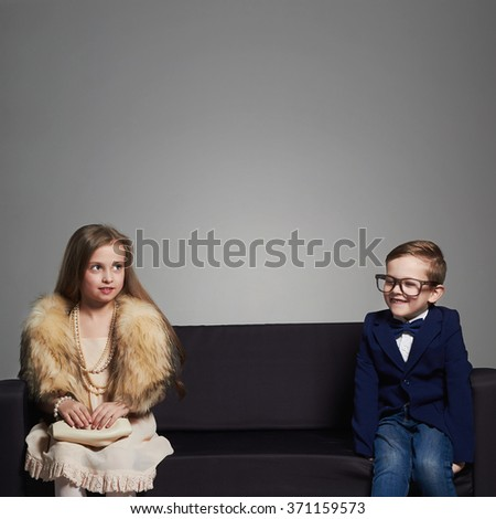 funny kids.beautiful couple on the couch.beauty little girl in dress and boy in suit and glasses