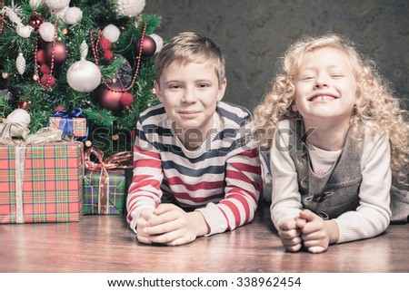 Funny kids, boy and girl lying on the floor under the Christmas tree. Next to the gifts. They are looking at the camera, smiling. Waiting for Christmas. Celebration. New Year. - stock photo