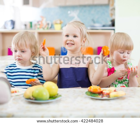 Funny kids eating oranges in day care centre - stock photo