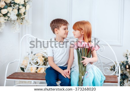Funny kids, happy little boy giving a cute girl bouquet of yellow spring flowers. Series in studio. Valentines Day, Mother's Day, 8 March, the birthday, the International Women's Day - stock photo