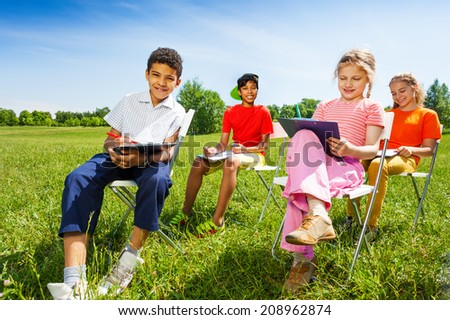 Funny kids hold sketch-boards and sit outside