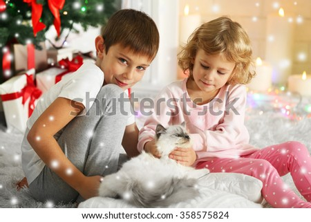 Funny kids with gift boxes and Christmas tree on background - stock photo