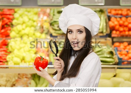 Funny Lady Chef Inspecting Vegetables with Magnifying Glass - Portrait of a young female cook in a grocery store checking for best quality ingredients   - stock photo