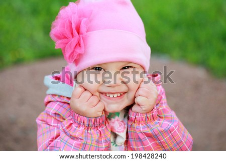 Funny laughing Caucasian baby girl in pink, outdoor portrait - stock photo
