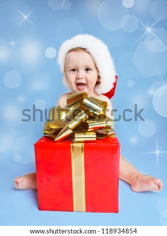 Funny laughing little boy in Santa hat sitting beside red Christmas present - stock photo