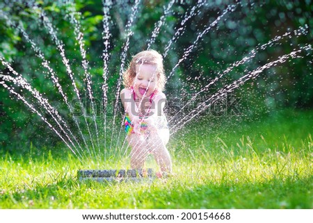 Funny laughing little girl in a colorful swimming suit running though garden sprinkler playing with water splashes having fun in the backyard on a sunny hot summer vacation day