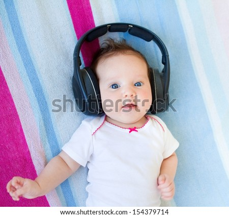 Funny laughing newborn baby relaxing on a colorful blanket listening to music with huge earphones - stock photo