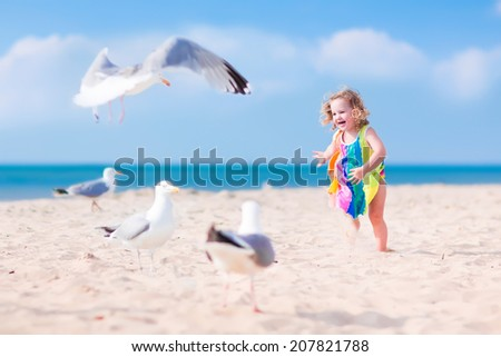 Funny laughing toddler, adorable little girl with curly hair in a colorful dress playing with seagull birds, running and jumping on a beautiful beach on a sunny hot summer day - stock photo