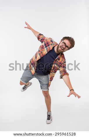 Funny life moments of bearded man. Man in T-shirt, shirt and jeans shorts fooling in photostudio on white background. - stock photo