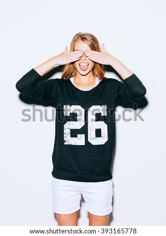 Funny lifestyle portrait beautiful blond crazy girl closes eyes with her hands and shows tongue, having fun, emotional and happy mood. Indoor. Hipster. - stock photo