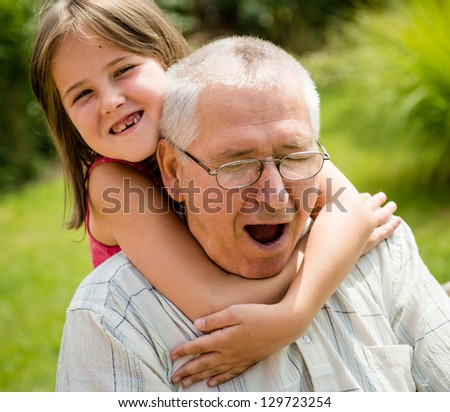Funny lifestyle portrait of grandchild embracing grandfather - stock photo