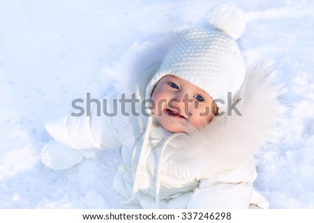 Funny little baby girl in a white knitted hat and warm white coat playing with snow. Kids play outdoors in winter. Children having fun at Christmas time. Child and infant cold weather clothing.  - stock photo