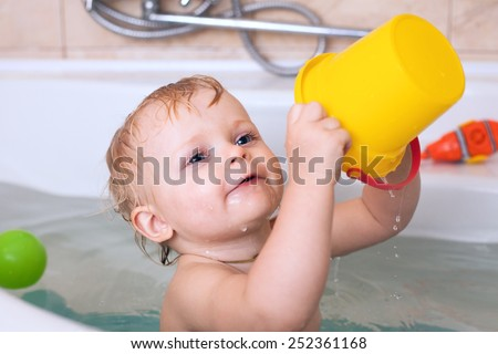 Funny little baby girl in the bath playing with water drops and splashes