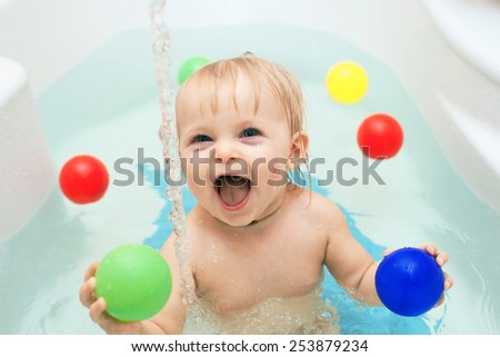 Funny little baby girl in the bath playing with water drops and splashes  - stock photo