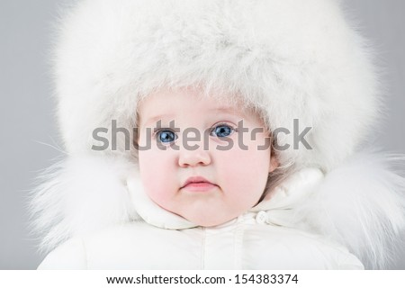 Funny little baby girl wearing a huge fur hat and a white warm snow jacket ready for a walk on a cold winter day - stock photo