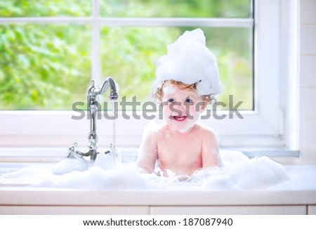 Funny little baby girl with wet curly hair taking a bath in a kitchen sink with lots of foam playing with water drops and splashes next to a big window with garden view - stock photo