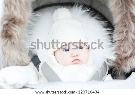 Funny little baby in a warm stroller on a cold winter day - stock photo