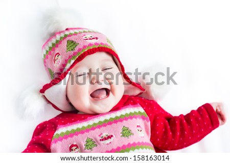 Funny little baby laughing and playing on a white blanket wearing Christmas decorated knitted hat and jacket - stock photo