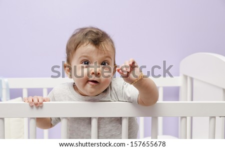 Funny little baby peeking out from the cradle - stock photo