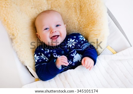 Funny little baby relaxing in a bouncer with sheepskin foot muff wearing warm knitted reindeer Christmas sweater at home on cold winter day. New born boy in stroller. Newborn child in rocking chair.  - stock photo