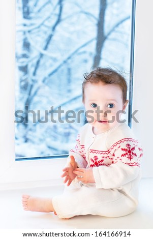 Funny little baby sitting next to a window to a garden with snow covered trees - stock photo