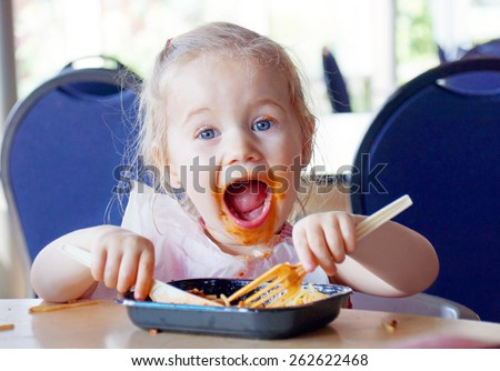 Funny little blond girl eating pasta and making a mess  - stock photo