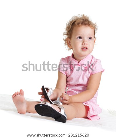 Funny little blonde girl in pink dress with pair of new shoes in hand - stock photo
