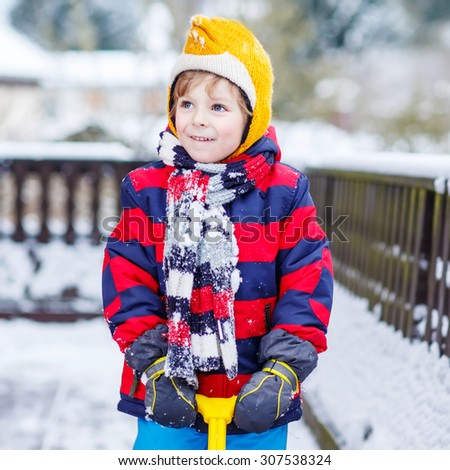 Funny little boy boy in colorful clothes happy about snow, playing and having fun, outdoors during snowfall on cold day. Active outdoors leisure with children in winter. - stock photo
