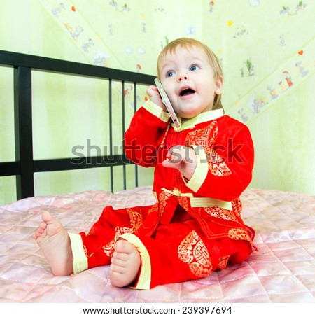 Funny little boy calls the room service in hotel by his telephone - stock photo