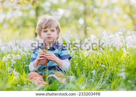 Funny little boy eating chocolate bunny and having fun outdoors at Easter holiday.