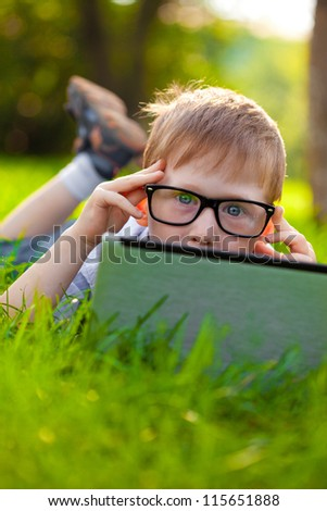 funny little boy looking from behind laptop in the park - stock photo