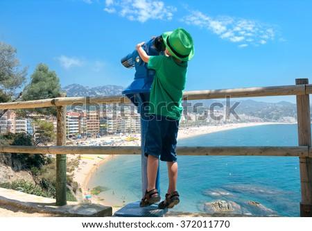Funny little boy looking in telescope at Lloret beach. Lloret de Mar. Catalonia, Costa Brava, Spain, Europe - stock photo