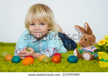 Funny little boy lying with Easter eggs  on green carpet