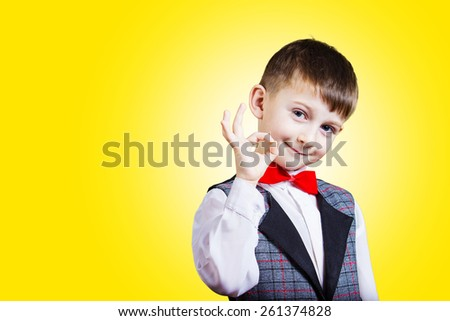 Funny Little boy making Ok sign over yellow background - stock photo