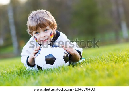 Funny little boy of 4 having fun with playing soccer with football on football field, outdoors. In white German national uniform and painted German flag on face.