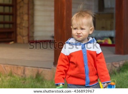 Funny little boy playing with garden tools outdoor