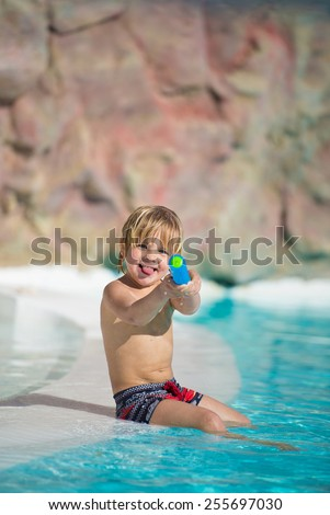 Funny little boy plays with water toy in the swimming pool - stock photo
