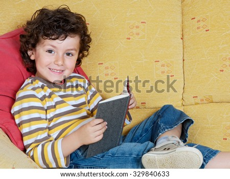 Funny little boy reading a book lying on the sofa
