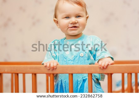 Funny little boy standing in the crib and smiling - stock photo