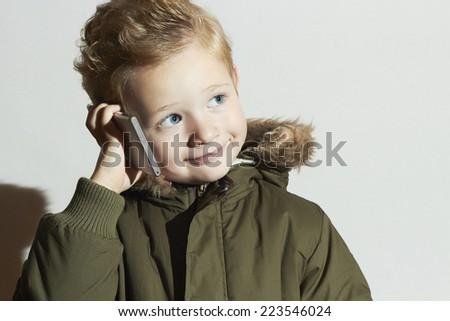 funny little boy talking on the cellphone. modern child in winter coat. fashion kids.children - stock photo